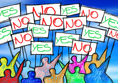 "A group of people protesting writing ""yes and no"" on their billboards"